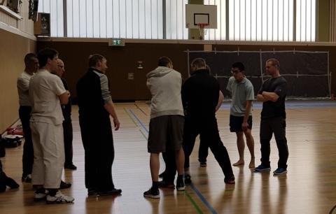 Gruppe mit Trainer der Realistische Selbstverteidigung ohne Waffen zeigt
